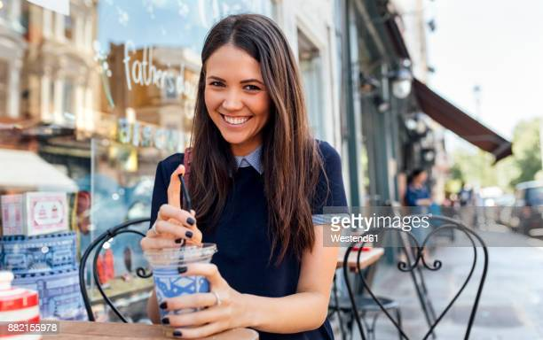UK, London, Nottinghill, portrait of happy young woman with beverage at pavement cafe
