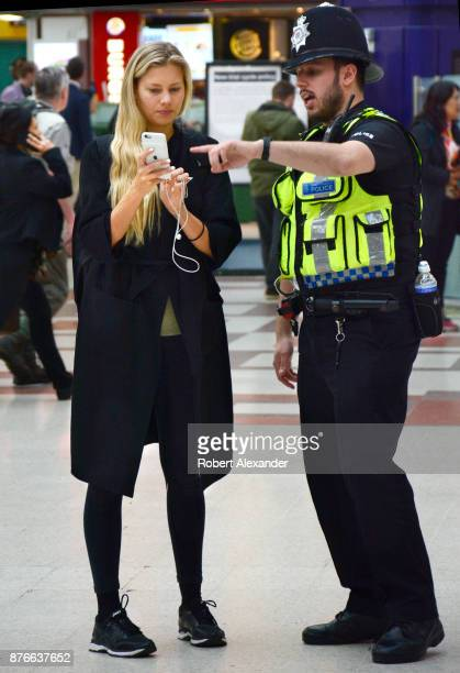 London police officer gives directions to a woman using her iPhone in busy London Victoria Station in London England a railway terminus and London...