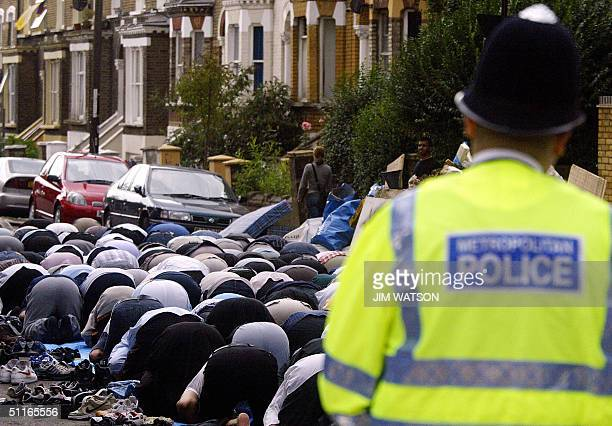 London police officer stands guard as Muslims pray outside the Finsbury Park Mosque during weekly friday prayers 13 August 2004 The mosque was not...
