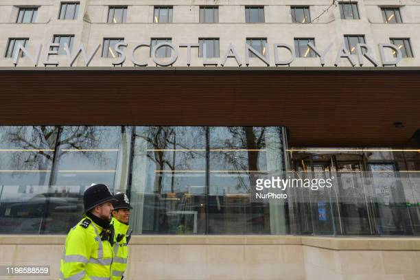London Police Officers walk near the entrance to New Scotland Yard office, the headquarters of the Metropolitan Police Service and the Police...