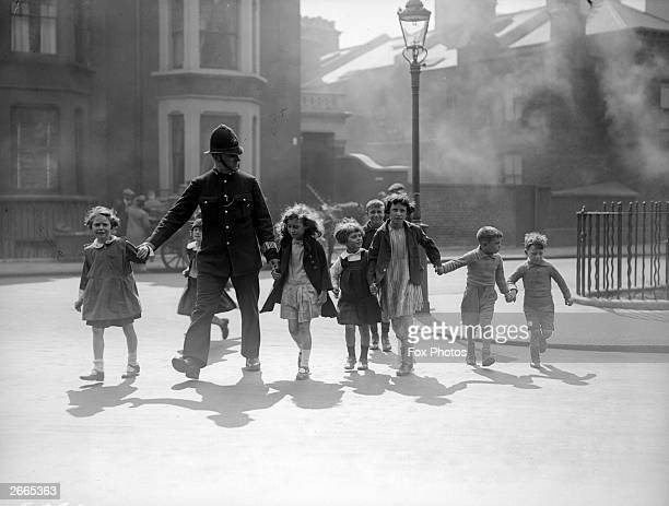 A London policeman escorts a group of children across a road at Chelsea