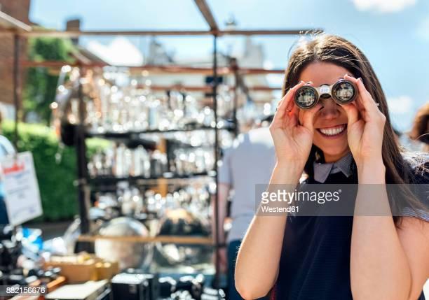 UK, London, Portobello Road, portrait of laughing woman looking through old binoculars