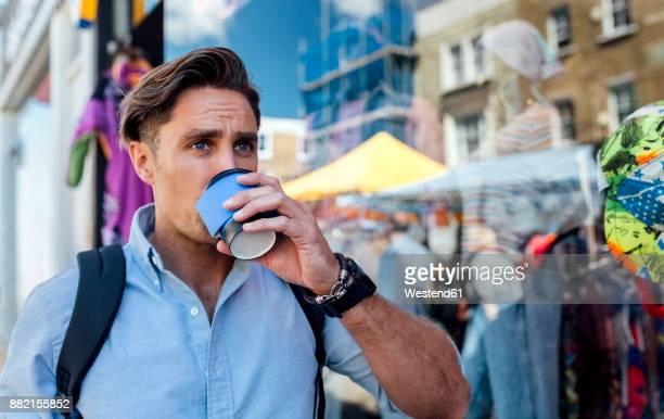 UK, London, Portobello Road, portrait of man drinking coffee in front of a shop window