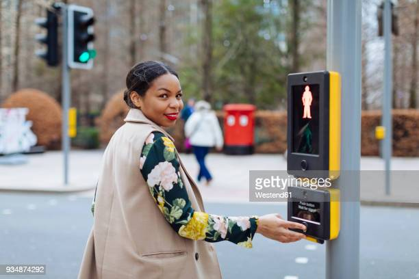 uk, london, portrait of smiling woman pressing button of pedestrian light - turning stock pictures, royalty-free photos & images