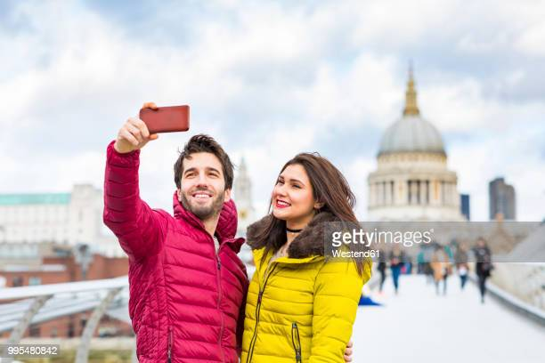 uk, london, portrait of smiling young couple taking selfie with cell phone in front of st pauls cathedral - tourism stock pictures, royalty-free photos & images