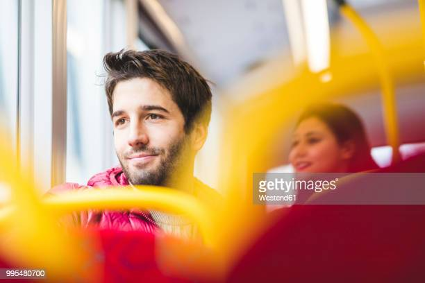 uk, london, portrait of smiling young man in bus looking out of window - autocarro imagens e fotografias de stock