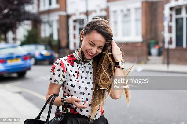 UK, London, portrait of smiling young woman with blowing hair