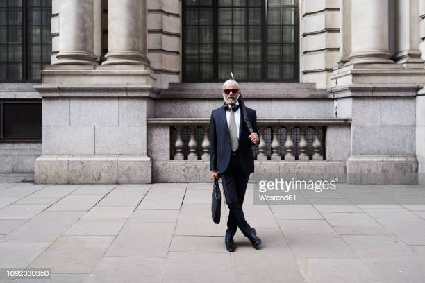 uk, london, portrait of stylish businessman with sunglasses and umbrella wearing suit and tie - eccentric stock pictures, royalty-free photos & images