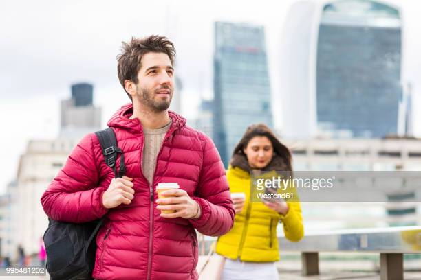 UK, London, portrait of young man with coffee to go and backpack wearing red down jacket