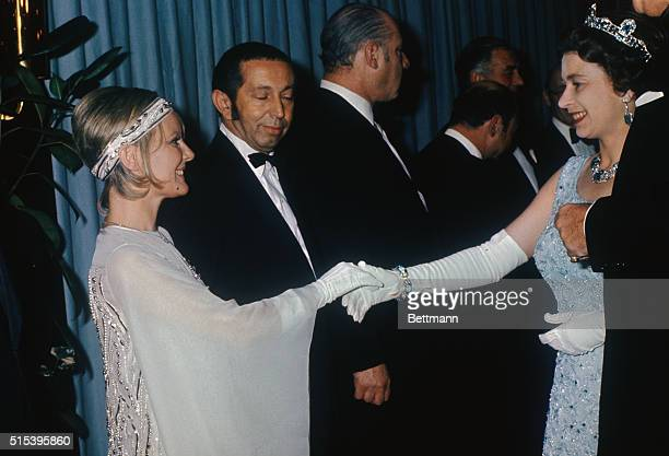 Queen Elizabeth II wearing sleeveless pale blue gown shakes hands with British born singer Petula Clark at premiere of Goodbye Mr Chips in which Miss...