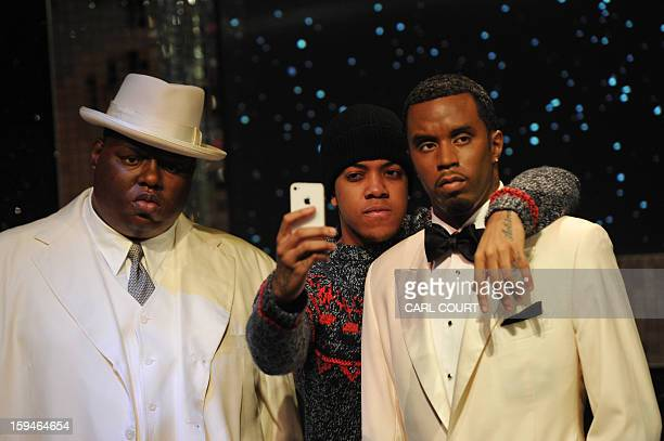 London rapper Chip poses with wax figures of US rappers The Notorious B I G and P Diddy at Madame Tussauds in central London on January 14 2013 to...