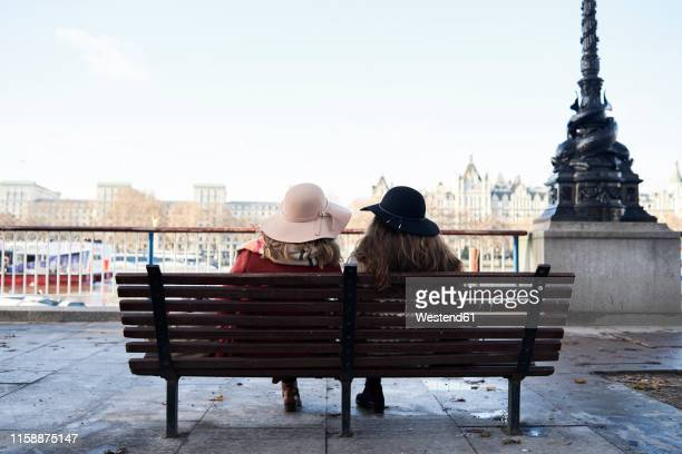 uk, london, rear view of two women sitting on a bench at river thames promenade - tourism stock pictures, royalty-free photos & images