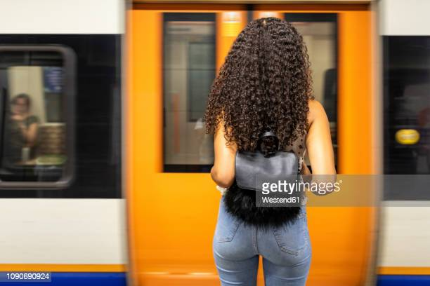 uk, london,  rear view of young woman waiting at underground station platform - london underground stock pictures, royalty-free photos & images