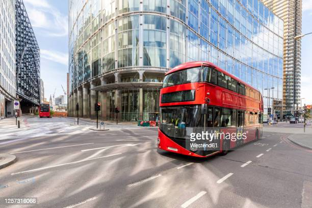 uk, london, red double decker bus # with modern buildings in background - bus stock pictures, royalty-free photos & images