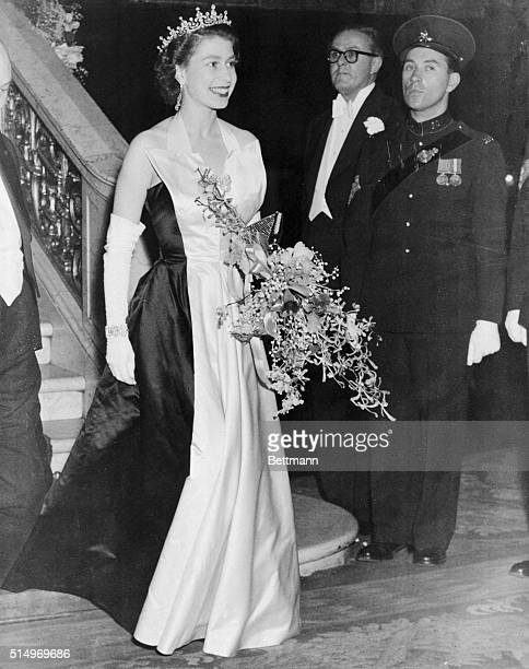 London: Royal Splendor. Wearing an elegant black-and-white satin gown, topped by a jeweled tiara, a radiant Queen Elizabeth II leaves the Empire...