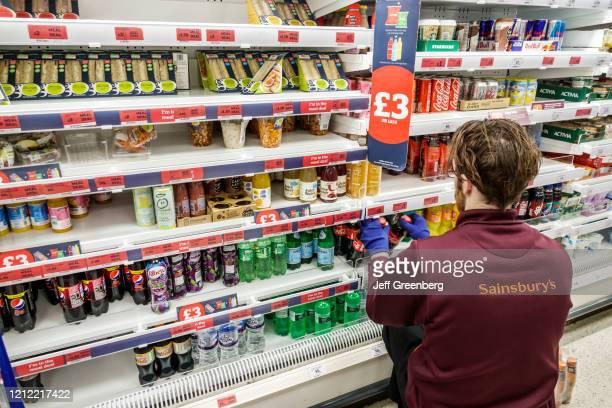 London, Sainsbury's supermarket, worker stocking refridgerated case.