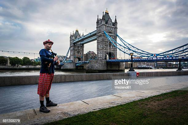 UK, London, Scottish bagpiper at Tower Bridge