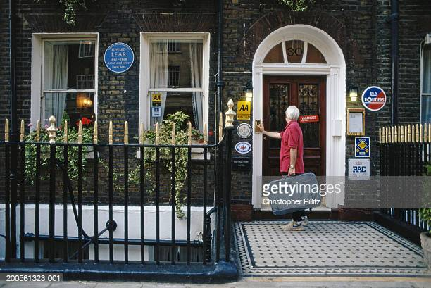 London, senior woman with suitcase standing by B&B, rear view.