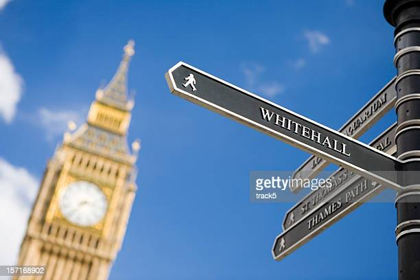 london sign directing towards whitehall with big ben in background - whitehall london stock photos and pictures