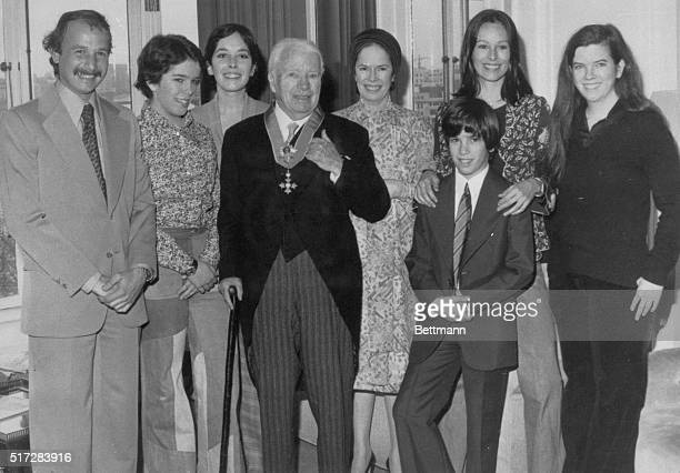 Sir Charles Chaplin wearing the insignia of the KBE with his family in his suite at the Savoy Hotel London after being knighted at Buckingham Palace...