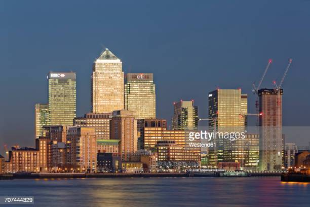 uk, london, skyline of canary wharf at river thames at dusk - canary wharf stock photos and pictures