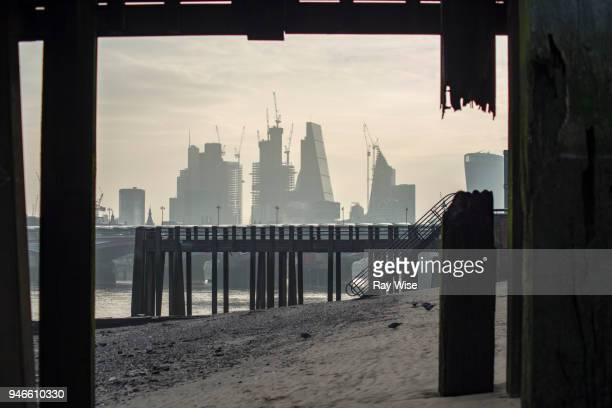 london skyline through the posts of a wooden pier. - low tide stock pictures, royalty-free photos & images