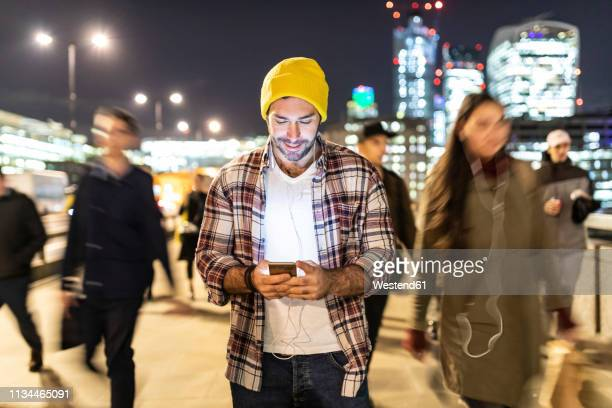 uk, london, smiling man looking at his phone by night with blurred people passing nearby - crowded stock pictures, royalty-free photos & images