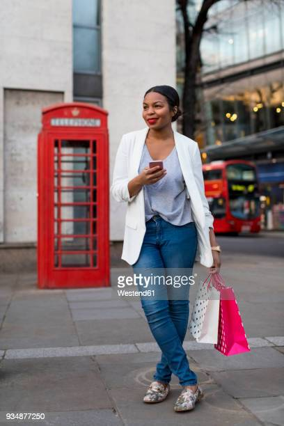 uk, london, smiling woman with cell phone holding shopping bags in the city - black jacket stock photos and pictures