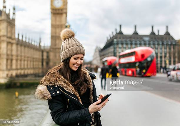 UK, London, smiling young woman looking at her smartphone in front of Palace of Westminster