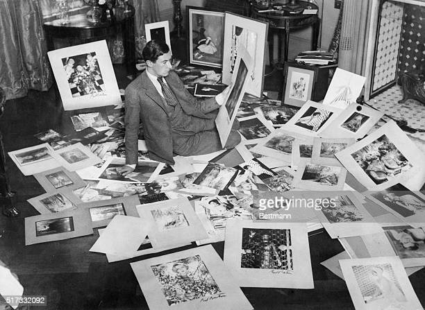 London society photographer Cecil Beaton sits on the floor making a choice from hundreds of pictures for an exhibition in New York