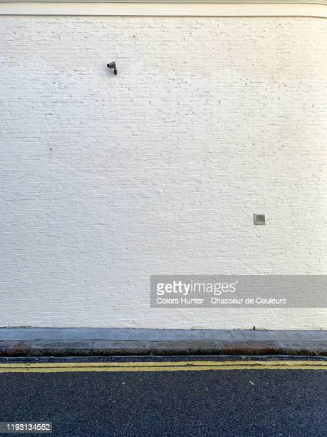london street and brick wall with surveillance camera - wall building feature stock pictures, royalty-free photos & images