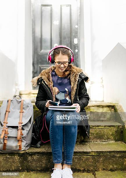 London, student girl with headphone and writing pad