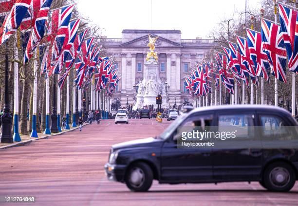 ロンドンのタクシーはちょうどウェストミンスター、セントラルロンドンのバッキンガム宮殿に向かってモールを断ろうとしています。 - ロンドン ザ・マル ストックフォトと画像