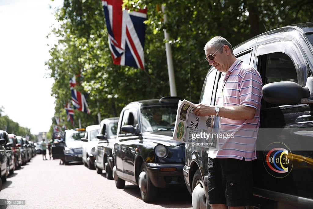 A London taxi driver leans against the diver's door of his cab as he reads 'The Badge' newspaper, whilst parked along The Mall, leading away from Buckingham Palace during a protest against Uber Technologies Inc.'s car sharing service in London, U.K., on Wednesday, June 11, 2014. Traffic snarled in parts of Madrid and Paris today, with a total of more than 30,000 taxi and limo drivers from London to Berlin blocking tourist centers and shopping districts. Photographer: Simon Dawson/Bloomberg via Getty Images