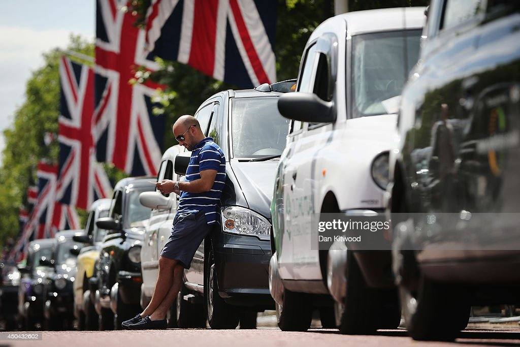 A London taxi driver looks at his phone on The Mall during a protest against a new smart phone app, 'Uber' on June 11, 2014 in London, England. London's licensed black taxi drivers are campaigning against the introduction of the 'Uber' taxi smartphone app in the United kingdom. Drivers say that there is a lack of regulation behind the new app.