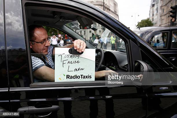 A London taxi driver places an identification board reading ' Totally Failing London' on the driver's window of his cab during a protest against Uber...