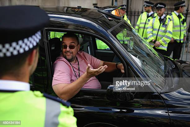 London taxi driver speaks with Police Officers during a protest against a new smart phone app 'Uber' on June 11 2014 in London England London's...