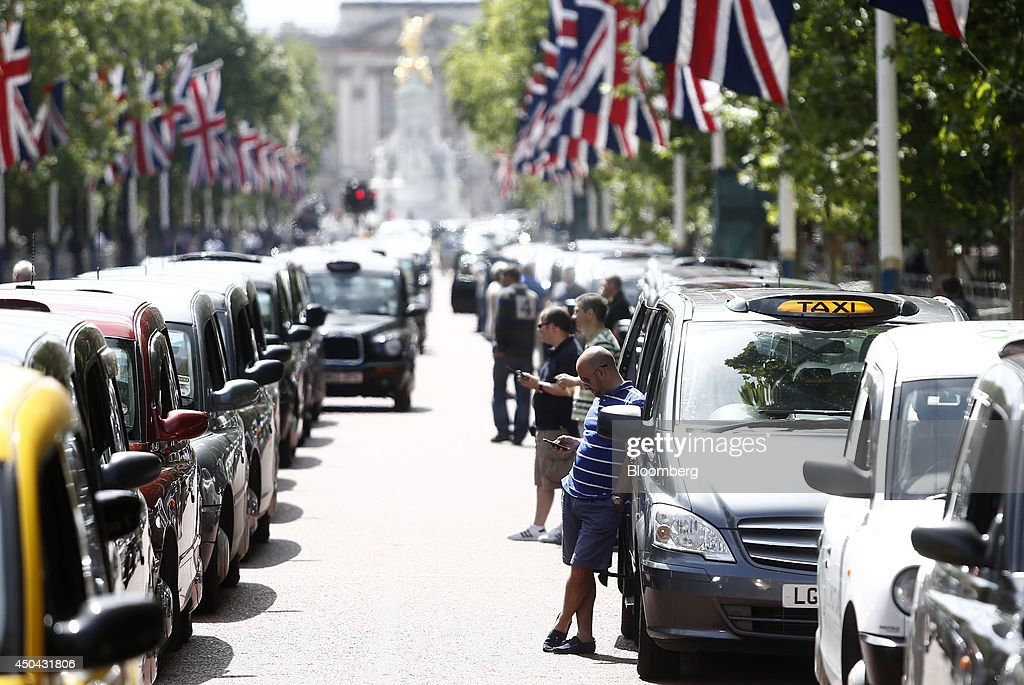 London taxi drivers use their smartphones as they stand alongside their parked cabs on The Mall, leading away from Buckingham Palace, during a protest against Uber Technologies Inc.'s car sharing service in London, U.K., on Wednesday, June 11, 2014. Traffic snarled in parts of Madrid and Paris today, with a total of more than 30,000 taxi and limo drivers from London to Berlin blocking tourist centers and shopping districts. Photographer: Simon Dawson/Bloomberg via Getty Images