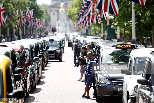 London taxi drivers use their smartphones as they stand alongside their parked cabs on The Mall leading away from Buckingham Palace during a protest...