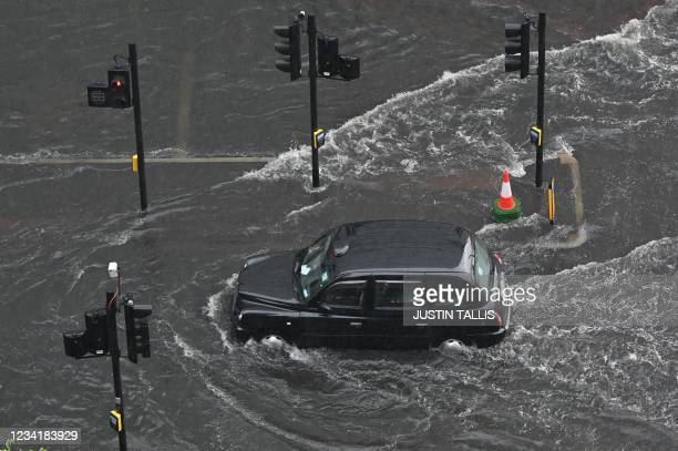 London taxi drives through water on a flooded road in The Nine Elms district of London on July 25, 2021 during heavy rain. - Buses and cars were left...