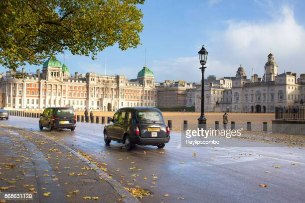 London Taxis driving past Horse Guards Palace in London, England on a sunny Autumn Day
