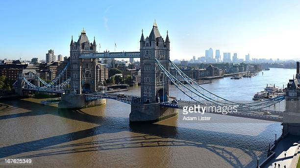 London - The iconic Tower Bridge spans the River Thames. Behind, in the morning sun, can be seen the business and financial district of Canary Wharf.