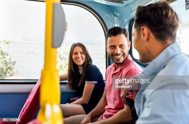 UK, London, three friends sitting in a double decker bus talking