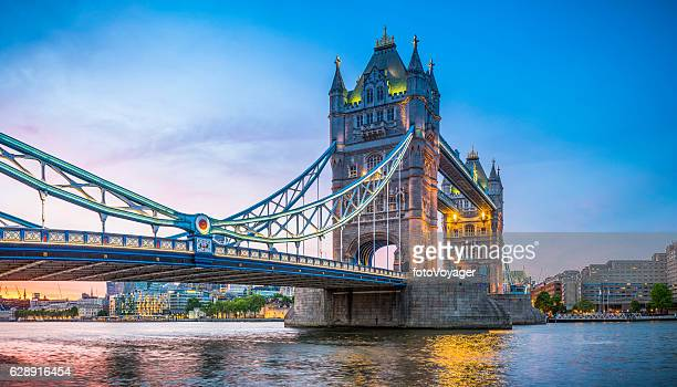 london tower bridge illuminated at sunset over river thames panorama - londres fotografías e imágenes de stock