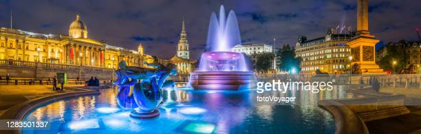 london trafalgar square fountains nelson's column panorama illuminated at night - national portrait gallery london stock pictures, royalty-free photos & images
