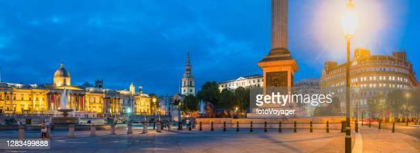 london trafalgar square nelson's column illuminated at dusk panorama uk - national portrait gallery london stock pictures, royalty-free photos & images