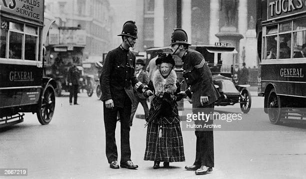 London traffic police escorting an elderly lady across a busy street in London