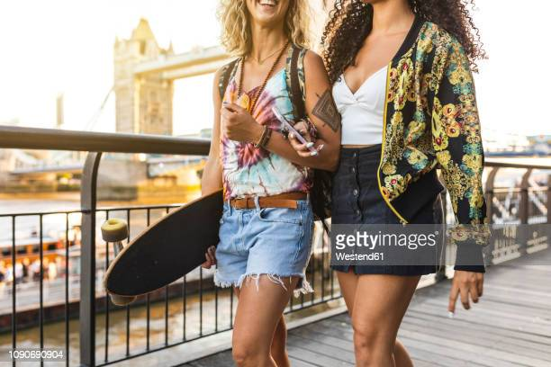 uk, london, two friends carrying a longboard with tower bridge in background at sunset - longboard skating stock pictures, royalty-free photos & images