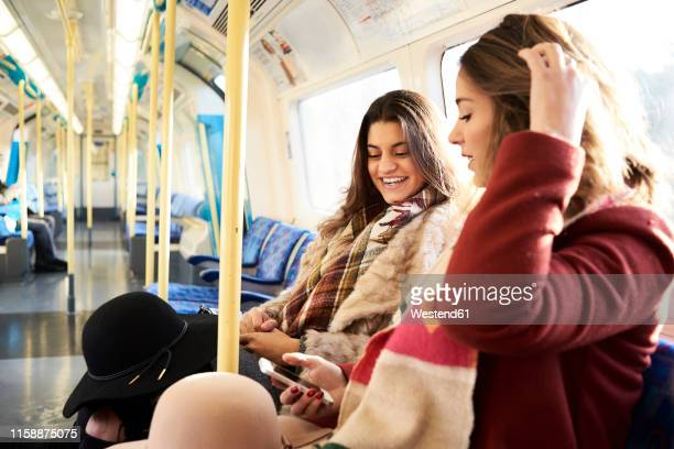 uk, london, two happy women in underground train using cell phone - travel stock pictures, royalty-free photos & images