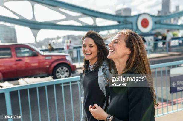 uk, london, two happy women walking on the tower bridge - tourism stock pictures, royalty-free photos & images
